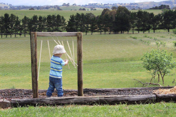 Child playing outdoor musical toy